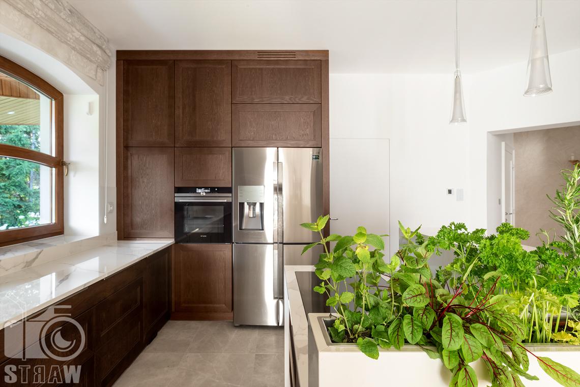 Fotografia wnętrz domu zaprojektowanego przez biuro projektowe, kuchnia, zielnik i zabudowa kuchenna w drewnie.