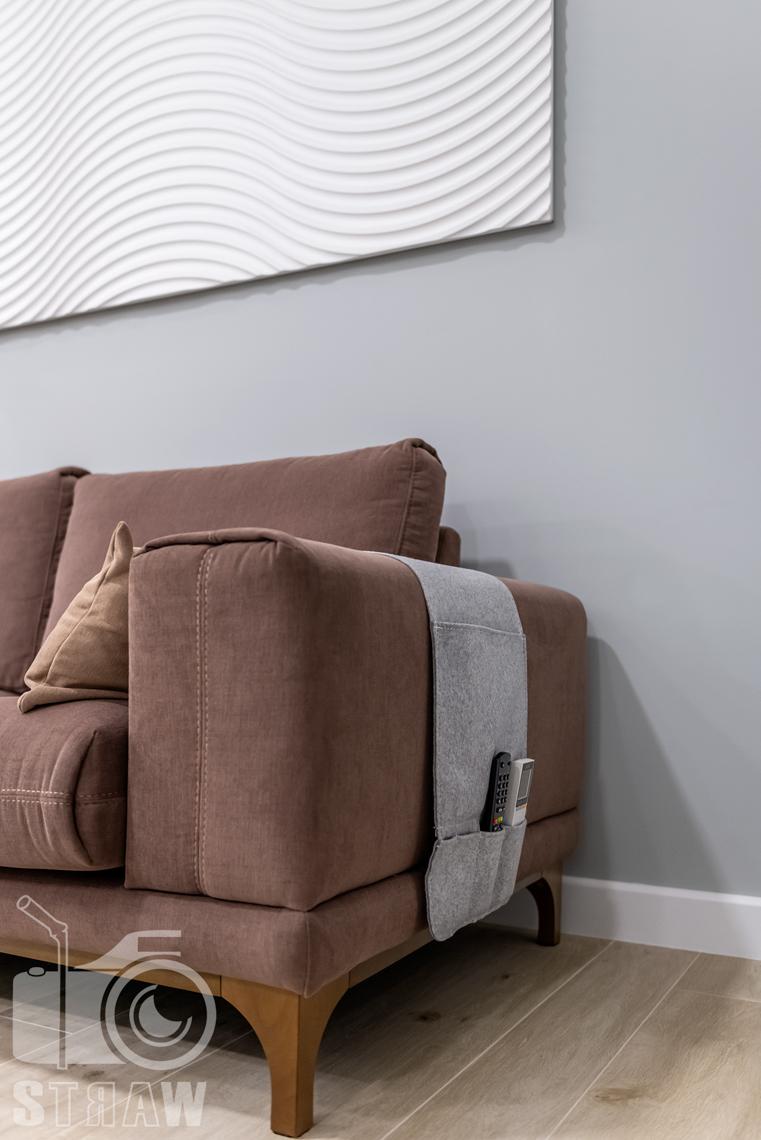 Fotografia nieruchomości na wynajem krótkoterminowy detale w salonie, niezbędnik na przybory powieszony na sofie.