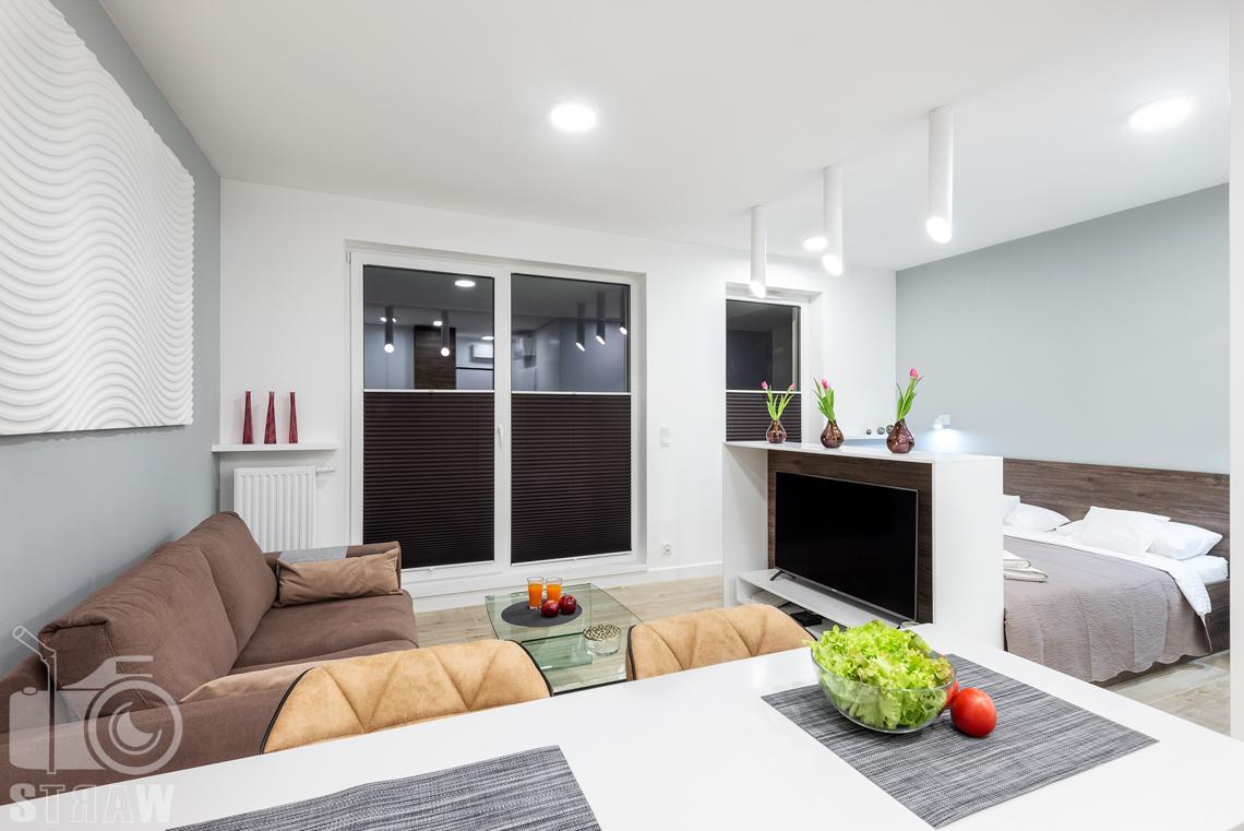 Fotografia nieruchomości na wynajem krótkoterminowy bufet kuchenny i stół w jednym, widok na salon i sypialnię.