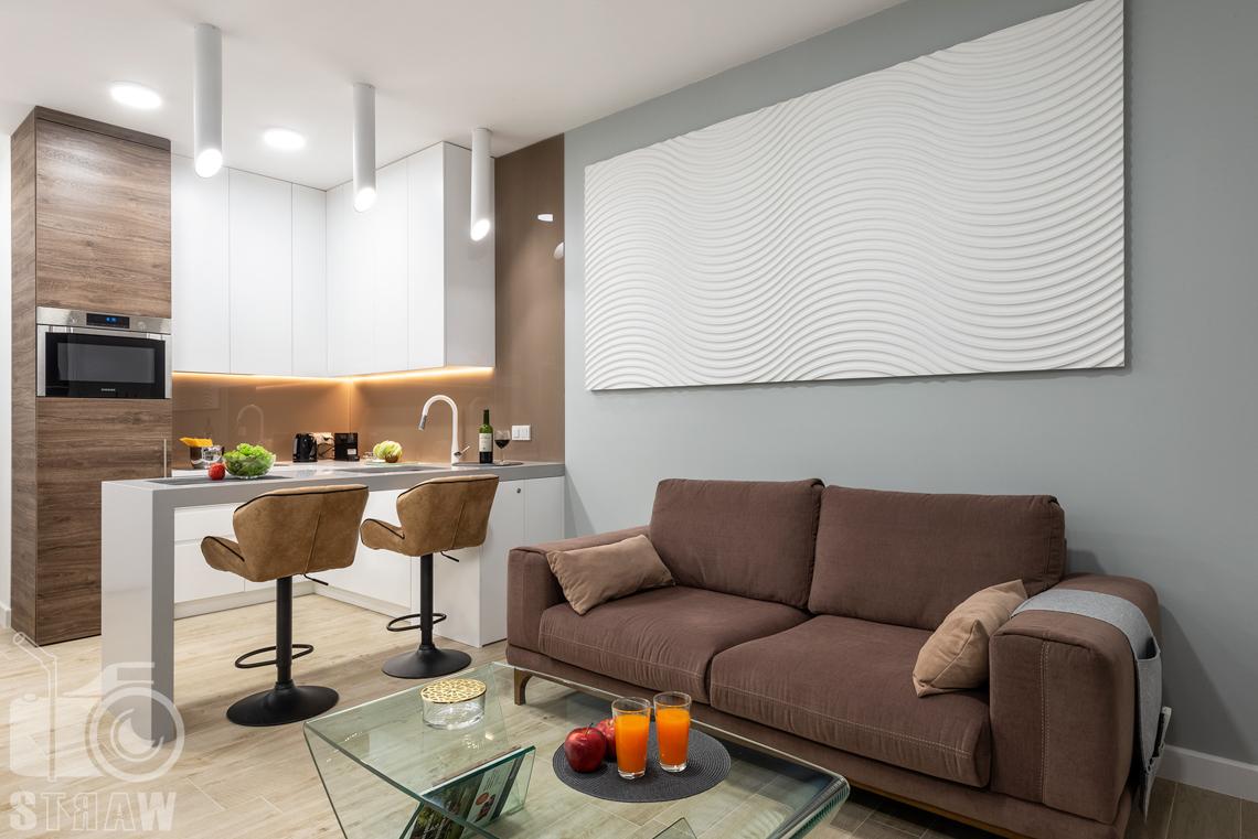 Fotografia nieruchomości na wynajem krótkoterminowy salon, sofa i stolik kawowy, widok na kuchnię.