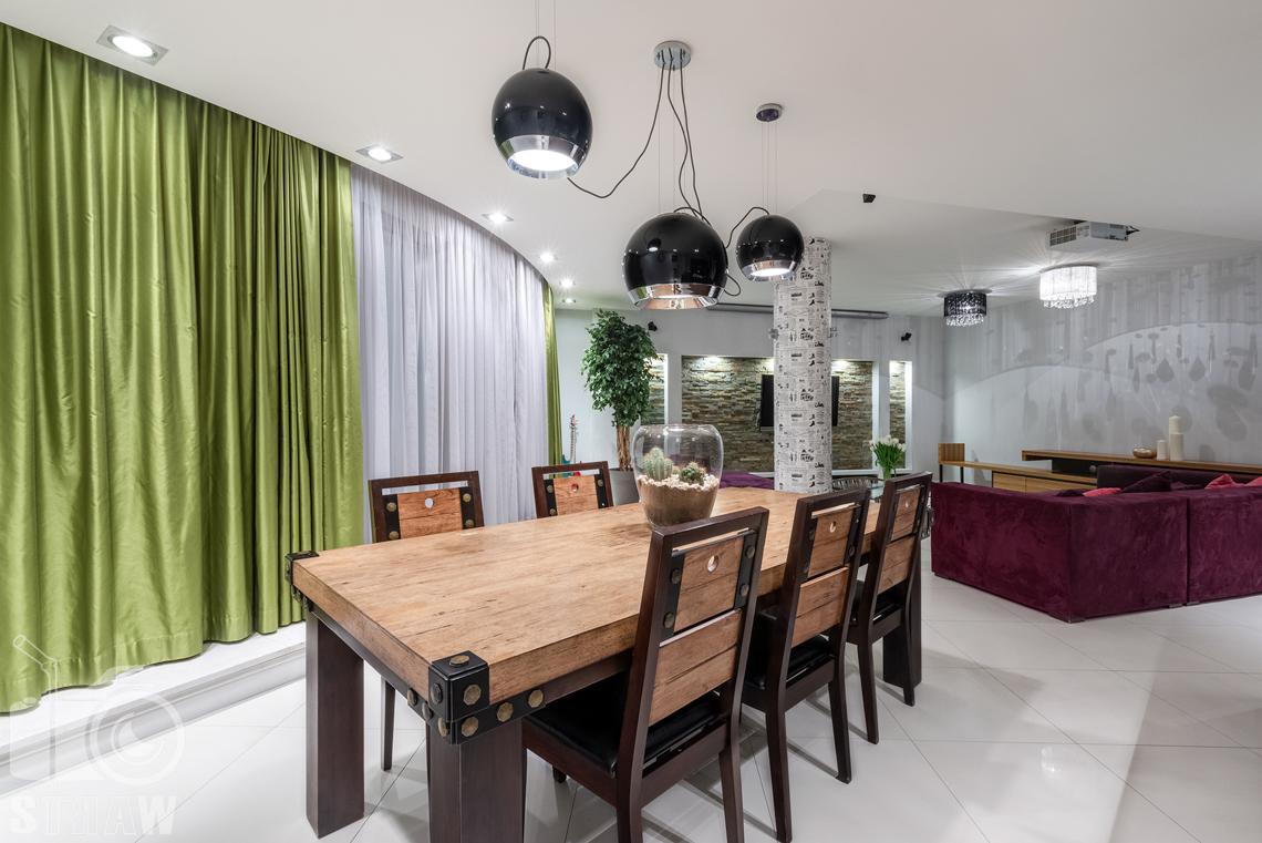 Fotografie mieszkania na sprzedaż w Warszawie, duży drewniany stół w jadalni.