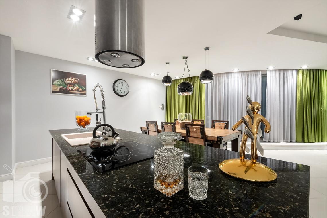 Fotografie mieszkania na sprzedaż, blat kuchenny i widok na stół w jadalni.