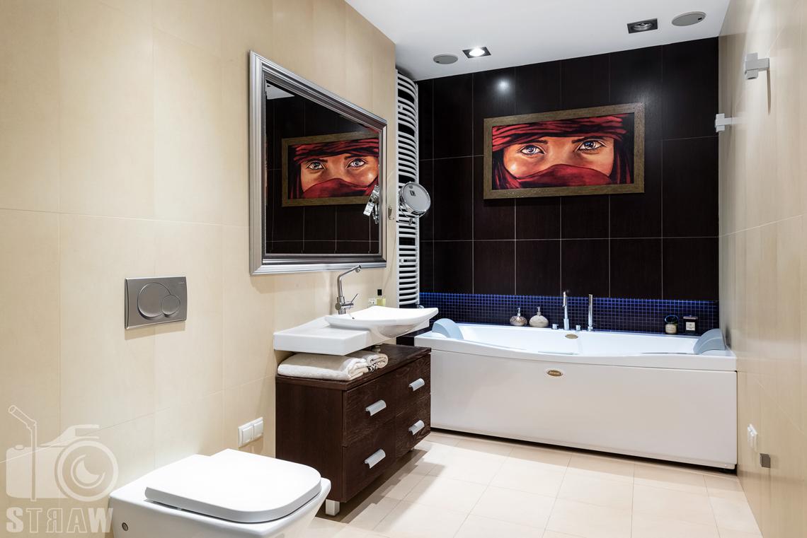 Fotografie mieszkania na sprzedaż, zdjęcie łazienki z wanną i obrazem.