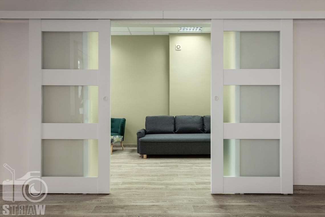Fotografia wnętrz komercyjnych, zdjęcia domu opieki medycznej, wejście do pokoju relaksu z rozsuwanymi drzwiami.