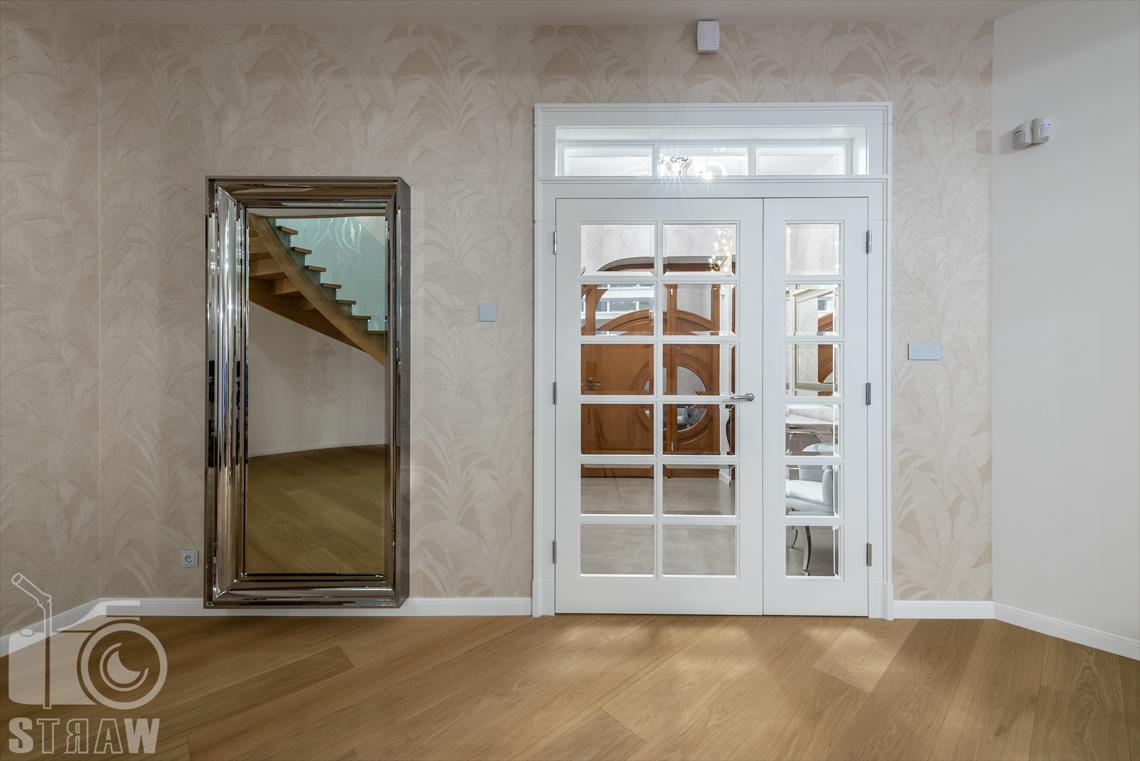 Fotografia wnętrz domu zaprojektowanego przez biuro projektowe, hol, przeszklone drzwi do przedpokoju i lustro.