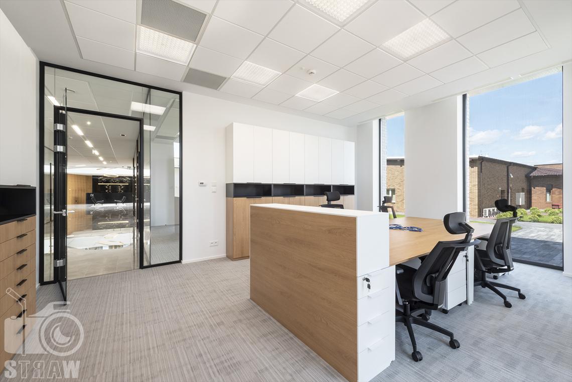 Sesja fotograficzna biura, zdjęcia wnętrz komercyjnych, pokój pracowniczy z czterema miejscami, biurkami i wyjściem w stronę recepcji.