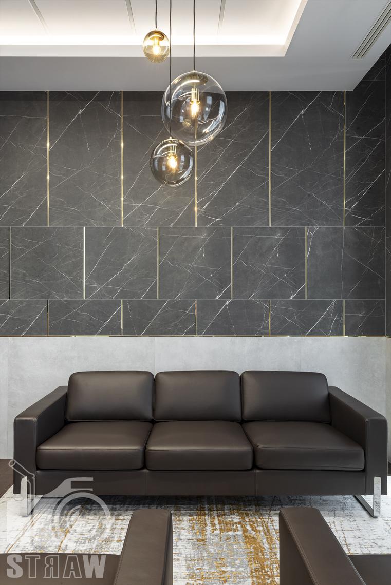 Sesja fotograficzna biura, zdjęcia wnętrz komercyjnych, sofa, żyrandol i ściana w gabinecie prezesa firmy nuco.