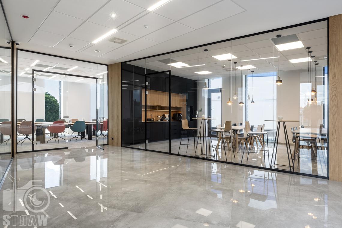 Sesja fotograficzna biura, zdjęcia wnętrz komercyjnych, kantyna firmowa oraz salka konferencyjna widziane z holu przez przeszklone ściany.