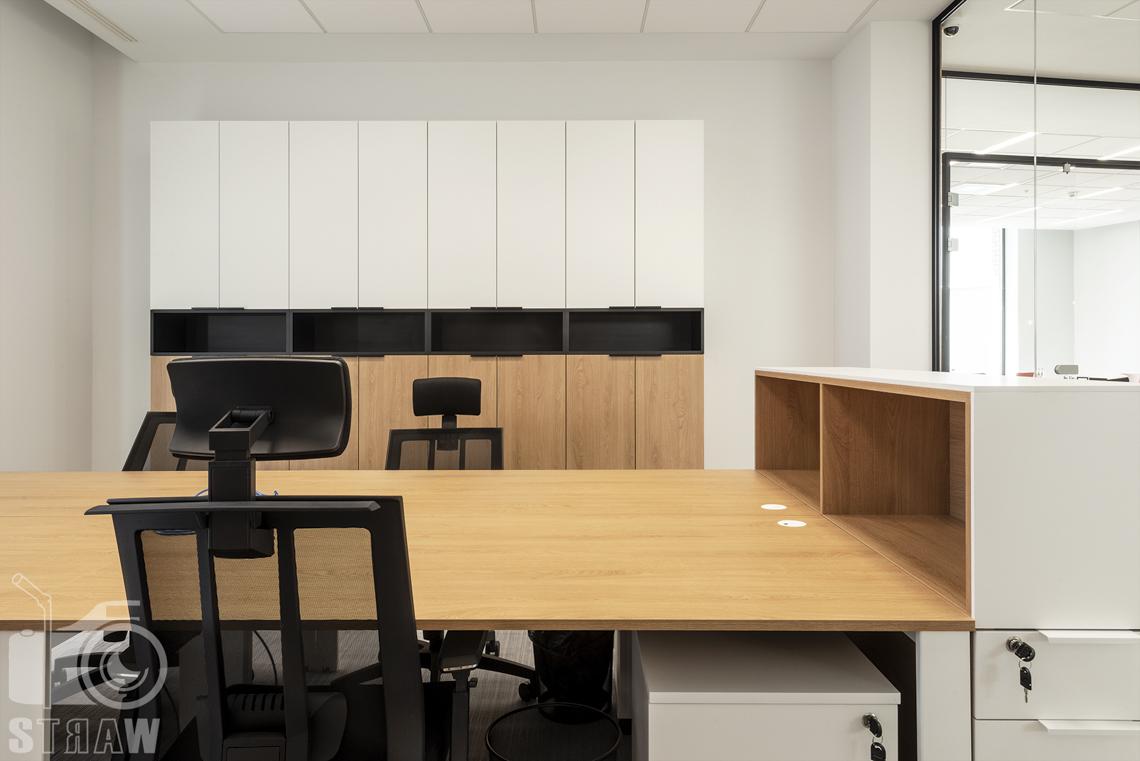 Sesja fotograficzna biura, zdjęcia wnętrz komercyjnych, pokój pracowniczy, fotel, biurko i szafki.