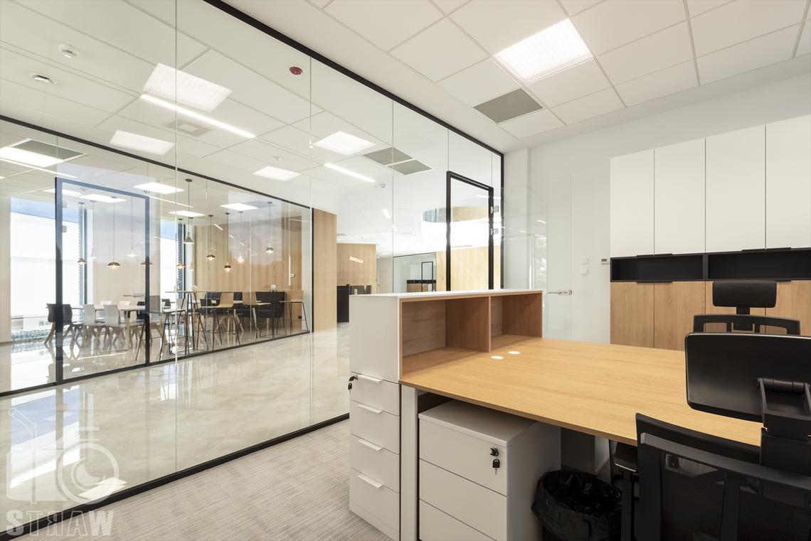 Sesja fotograficzna biura, zdjęcia wnętrz komercyjnych, pokój pracowniczy na parterze ze szklanymi ścianami, widok na kantynę.