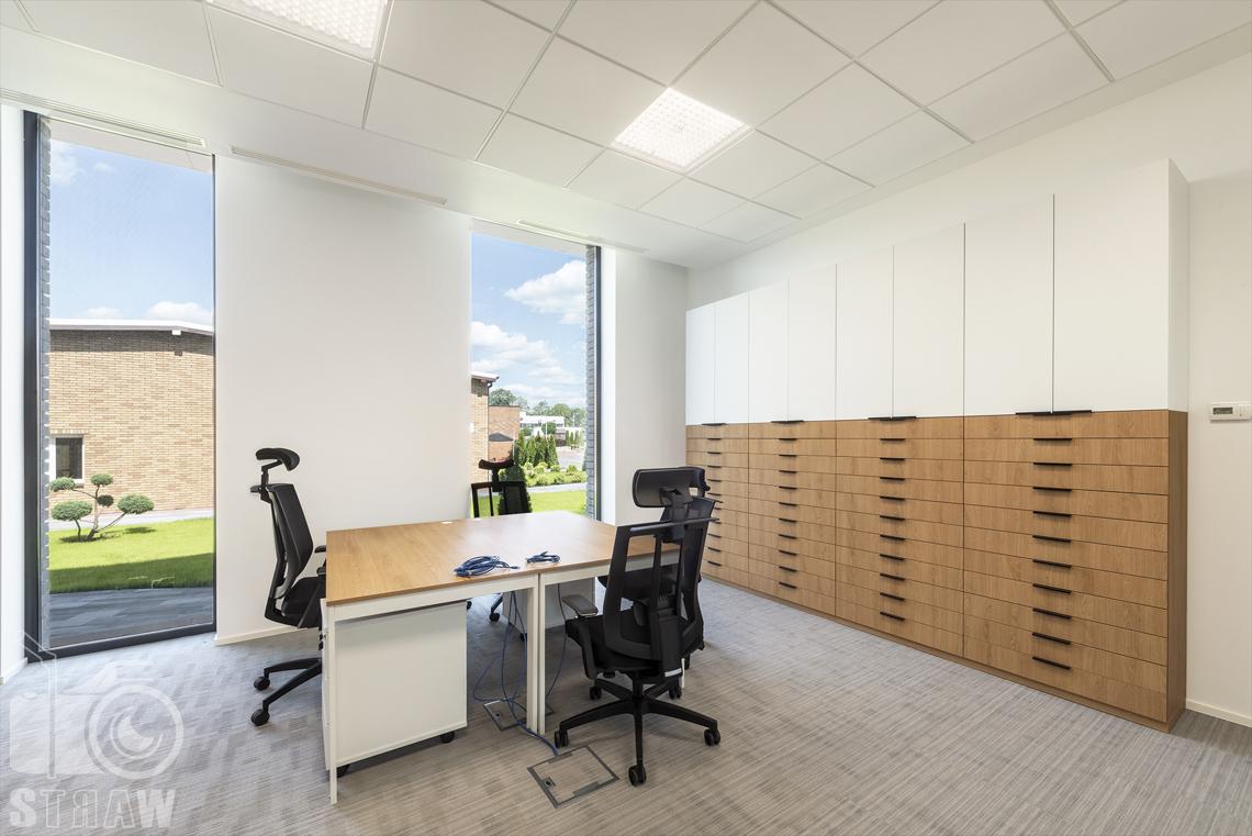 Sesja fotograficzna dla agencji projektowej, zdjęcia wnętrz komercyjnych, salka pracownicza z biurkami i szafkami na kosmetyki.