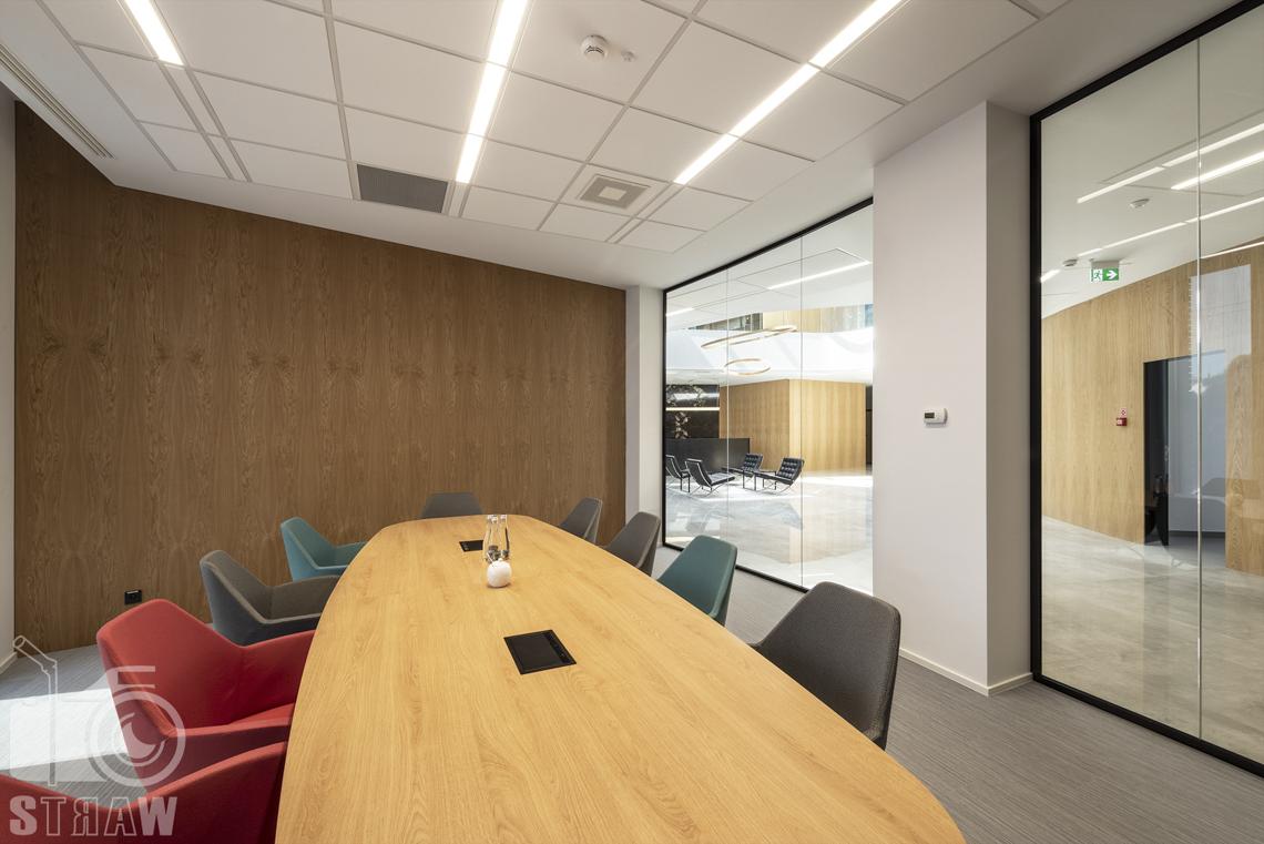 Sesja fotograficzna dla biura projektowego, zdjęcia wnętrz komercyjnych, owalny stół w salce konferencyjnej, szklane ściany widok na recepcję.