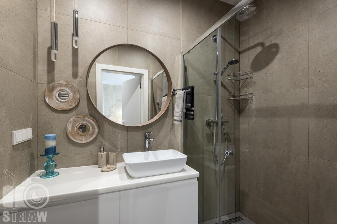 Fotograf wnętrz i zdjęcia nieruchomości na wynajem, łazienka w tonacji brązu z prysznicem, umywalką i lustrem okrągłym.