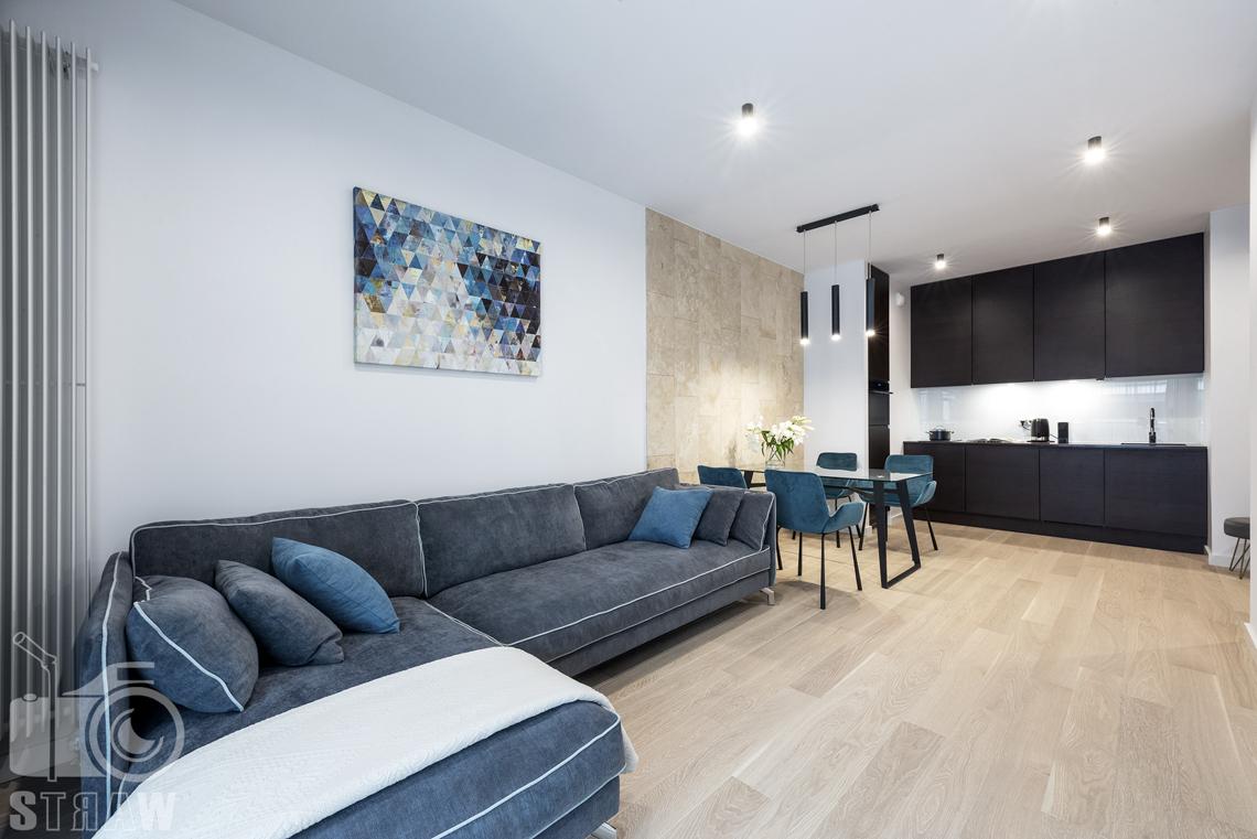 Fotograf wnętrz i zdjęcia nieruchomości na wynajem, salon i otwarta kuchnia, stół w jadalni i duża sofa.