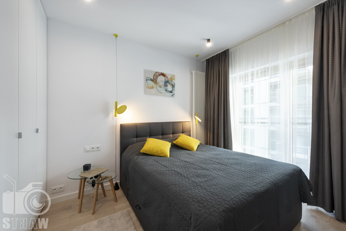 Fotograf wnętrz i zdjęcia nieruchomości na wynajem, sypialnia z żółtymi lampkami i poduszkami, łóżko obraz i stoliki z przezroczystymi blatami.nia