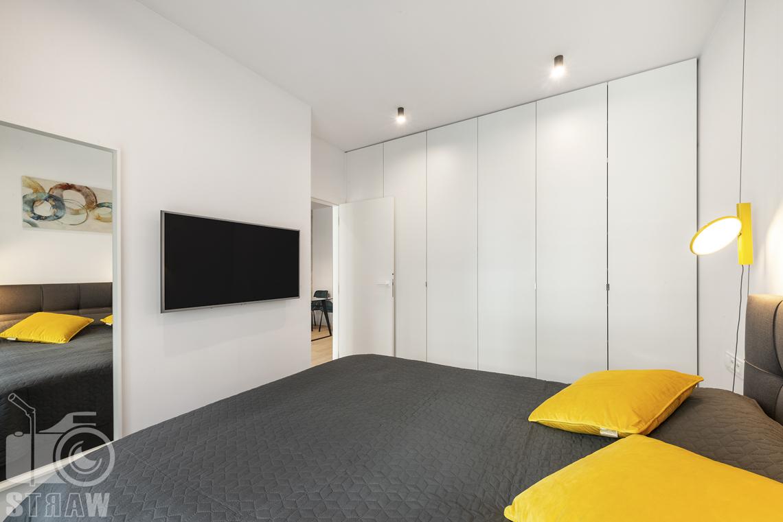 Fotograf wnętrz i zdjęcia nieruchomości na wynajem, sypialnia w niej lustro i łóżko z żółtymi poduszkami.