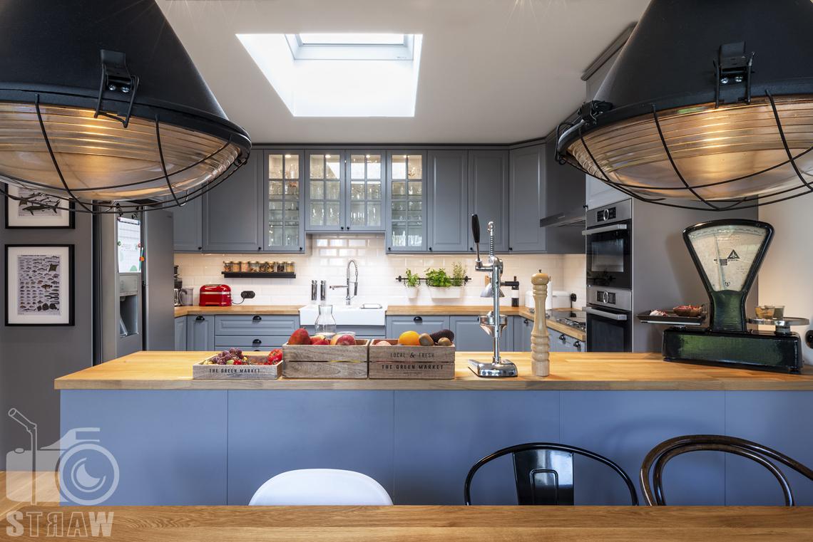 Zdjęcia nieruchomości na sprzedaż, lampy wiszące w kuchni, blat z owocami.