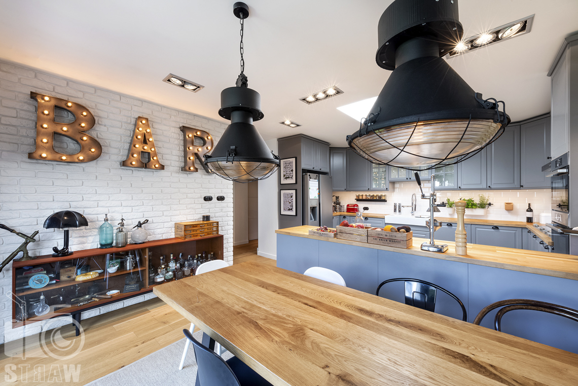 Zdjęcia nieruchomości na sprzedaż, kuchnia z jadalnią, stół, lampy, szafki i blaty.