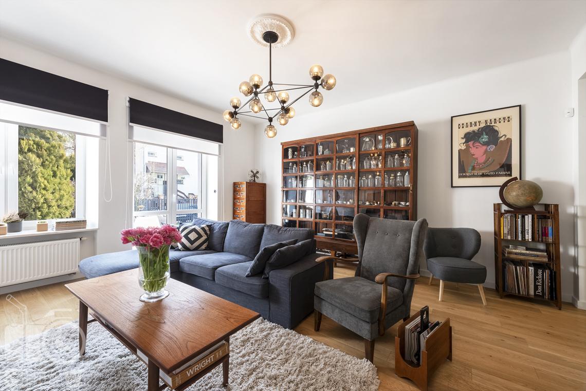 Zdjęcia nieruchomości na sprzedaż, salon z sofą i fotelem, żyrandol, przeszklona witryna i stół.