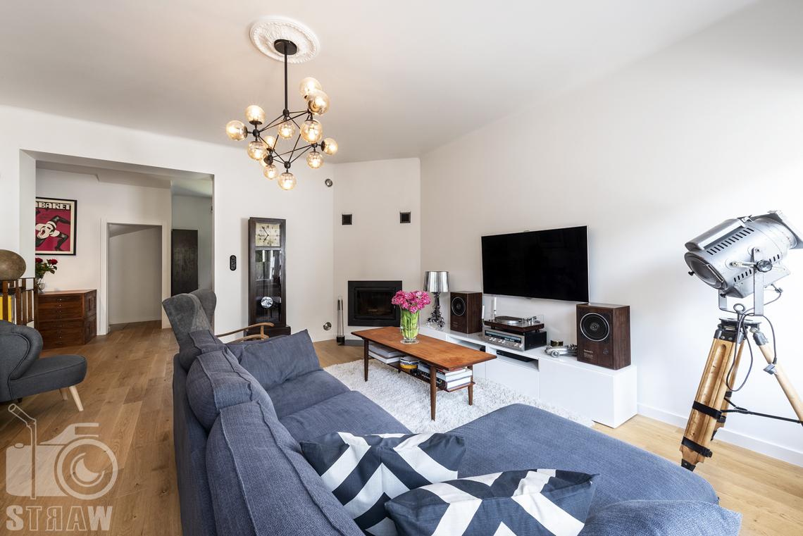 Zdjęcia nieruchomości na sprzedaż, salon z sofą, stołem i telewizorem, stojący zegar drewniany.