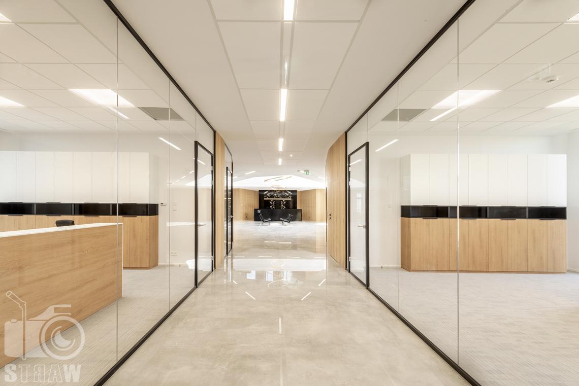 Sesja fotograficzna biura, zdjęcia wnętrz komercyjnych, hol biura z przeszklonymi gabinetami oraz z widokiem na recepcję.