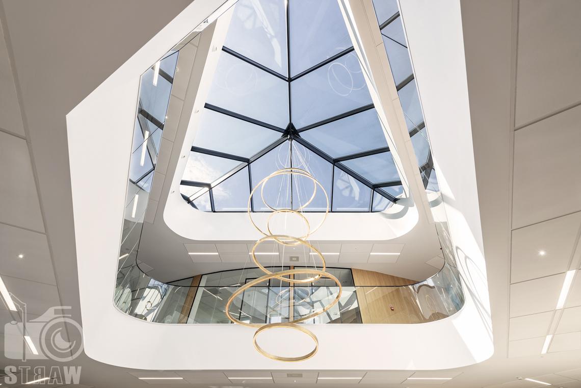 Sesja fotograficzna biura, zdjęcia wnętrz komercyjnych, wisząca kołowa lampa spod szklanego sufitu.