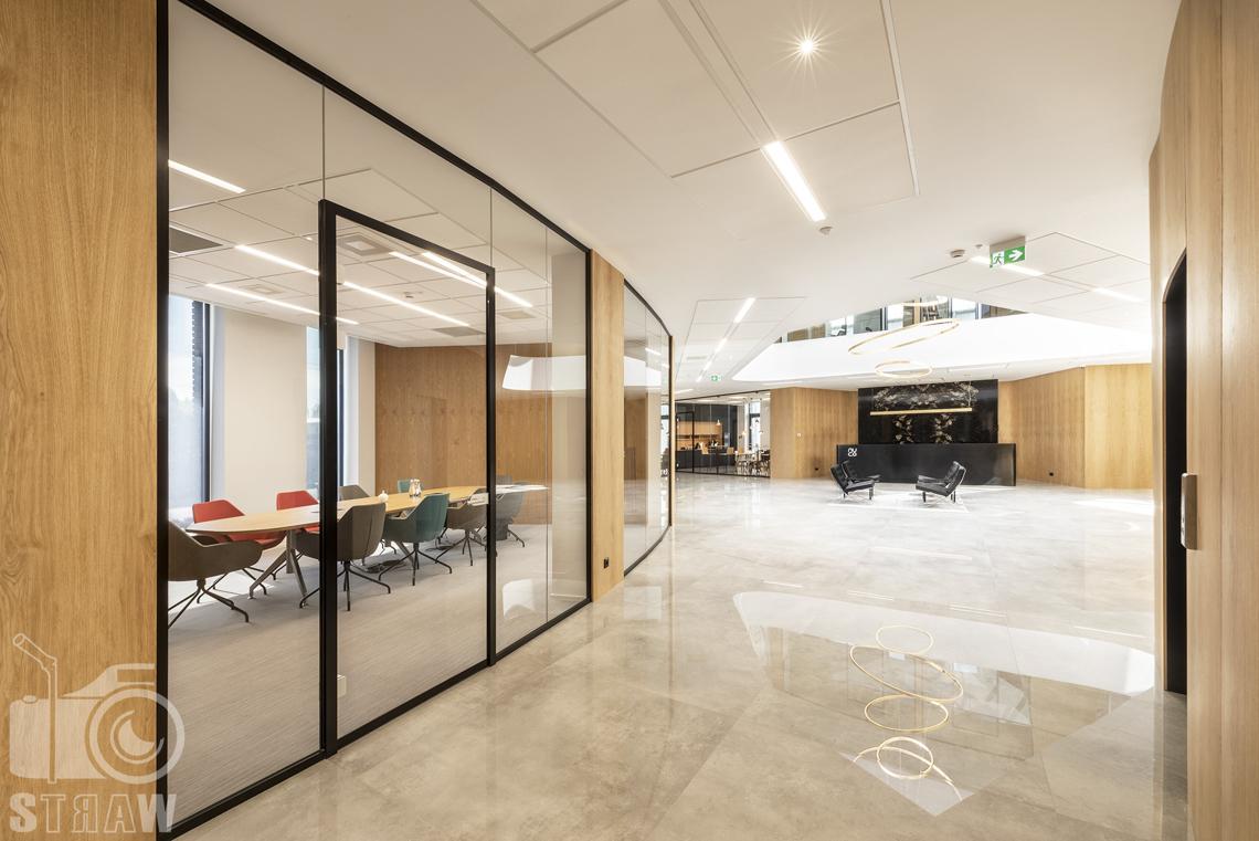 Sesja fotograficzna biura, zdjęcia wnętrz komercyjnych, hol, widok na recepcję i przeszkloną salę konferencyjną.