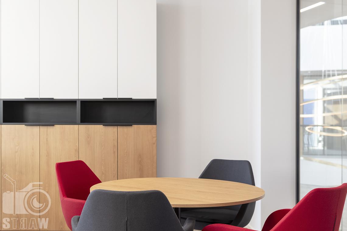 Sesja fotograficzna biura, zdjęcia wnętrz komercyjnych, kolorowe fotele, stół i szafki.