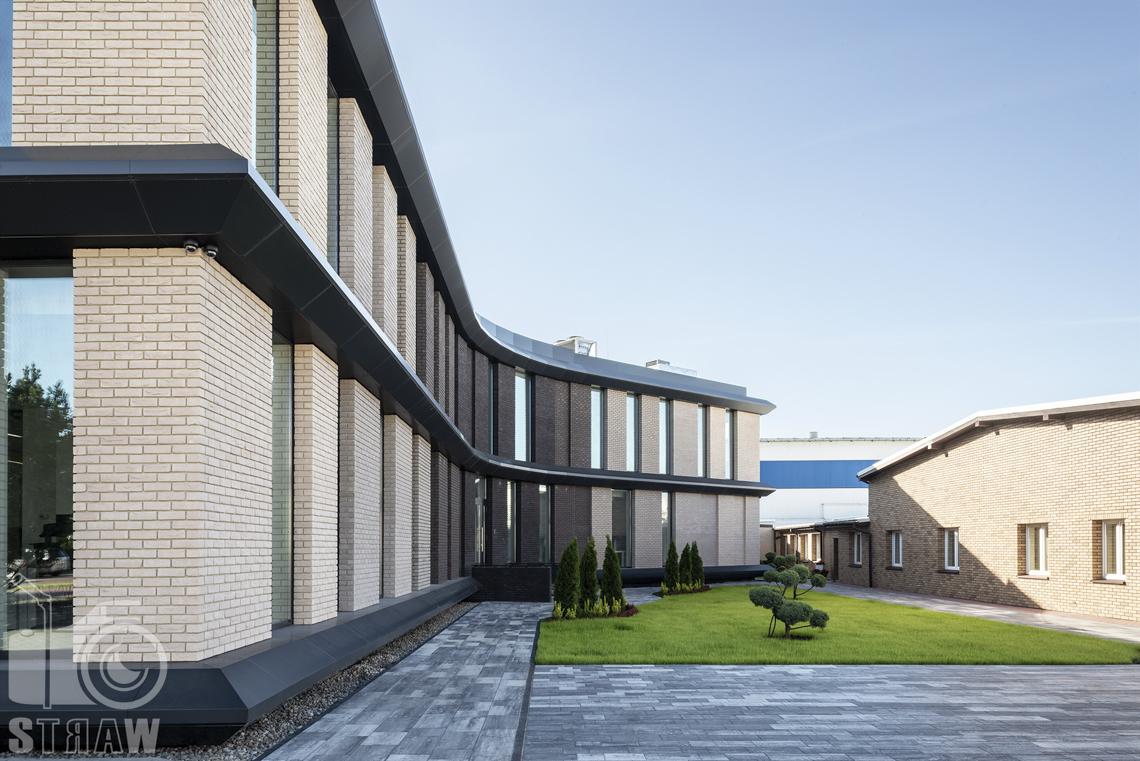 Sesja fotograficzna biura, zdjęcia wnętrz komercyjnych, budynek z zewnątrz oraz patio z krzewami.