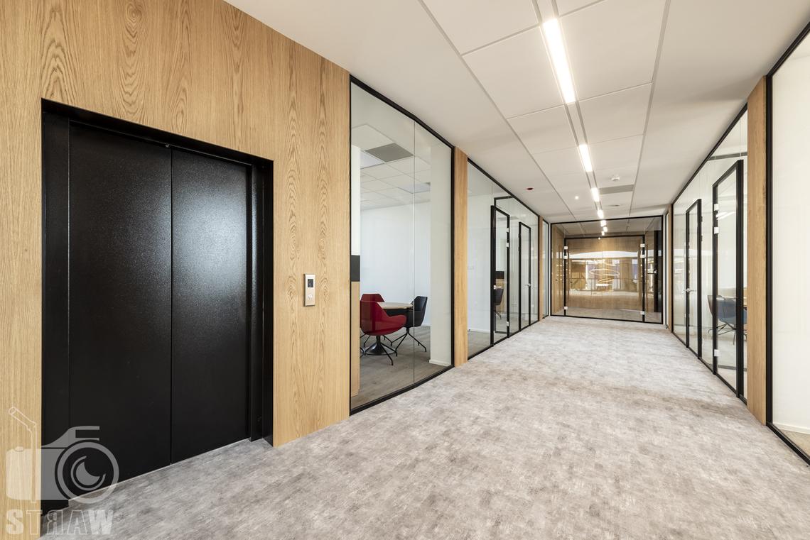 Sesja fotograficzna biura, zdjęcia wnętrz komercyjnych, korytarz i przeszklone gabinety oraz winda.