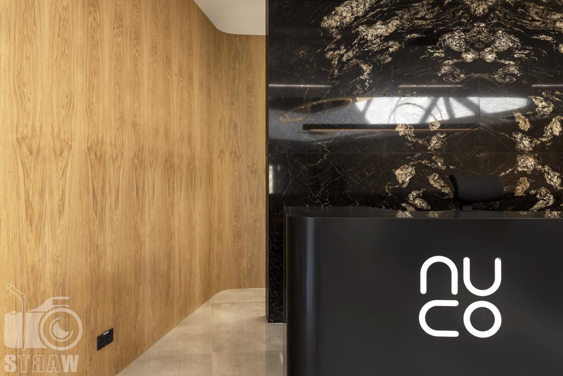 Sesja fotograficzna biura, zdjęcia wnętrz komercyjnych, detale w recepcji, marmurowa ściana i logo firmowe.