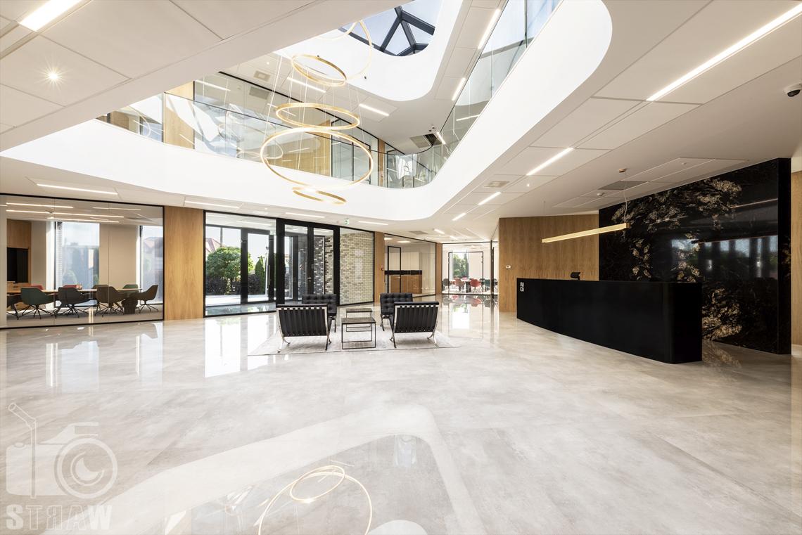 Sesja fotograficzna biura, zdjęcia wnętrz komercyjnych, hol z lampą wiszącą z piętra do holu, widok na salki konferencyjne.