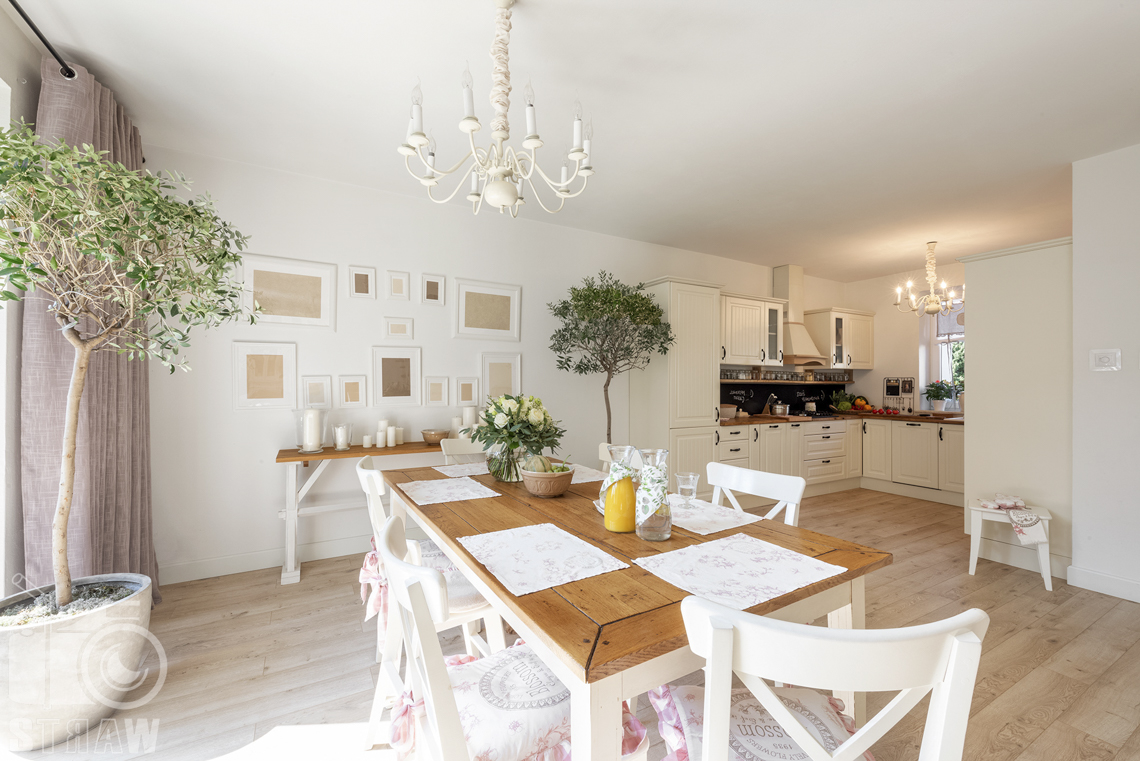 Fotografia wnętrz nieruchomości na sprzedaż Warszawa, drewniany stół w jadalni, biało drewniana kolorystyka wnętrza.