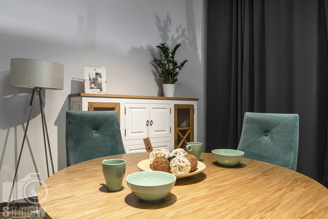 Fotografia wnętrz komercyjnych, zdjęcia showroomu meblowego, blat drewnianego stołu okrągłego z dekoracjami.