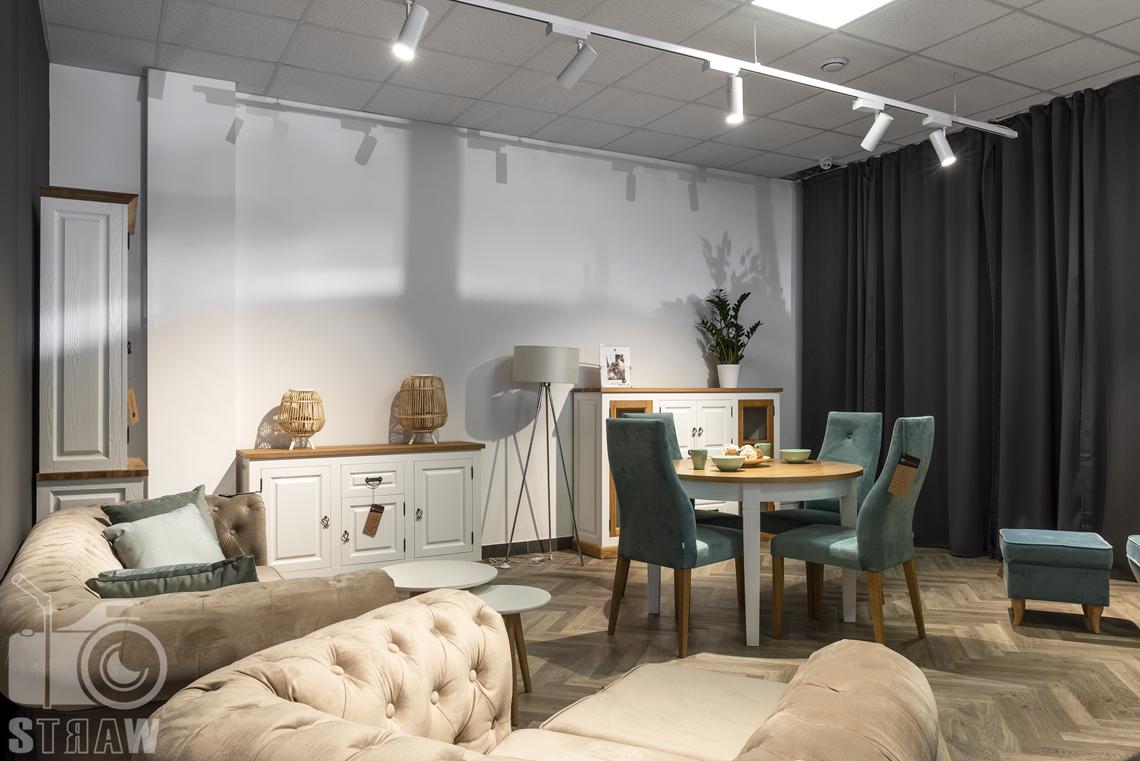Fotografia wnętrz komercyjnych, zdjęcia showroomu meblowego, na zdjęciu sofa, fotel, okrągły stół i pikowane krzesłą w kolorze morskim.