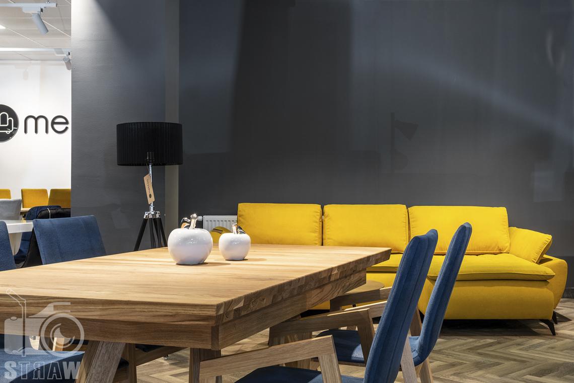Fotografia wnętrz komercyjnych, zdjęcia sklepu meblowego, drewniany stół i niebieskie meble, w tle żółta sofa.