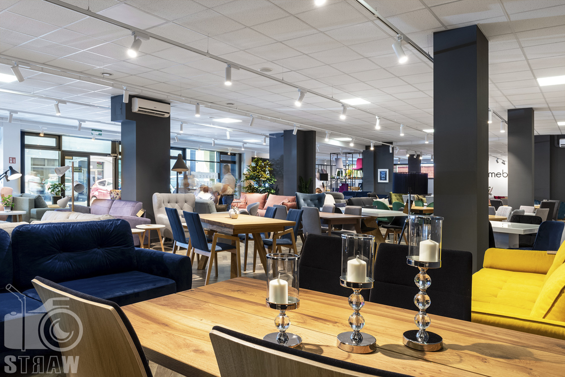 Fotografia wnętrz komercyjnych, zdjęcia sklepu meblowego Mebloo w Łodzi, na pierwszym planie blat drewnianego stołu ze świecznikami.