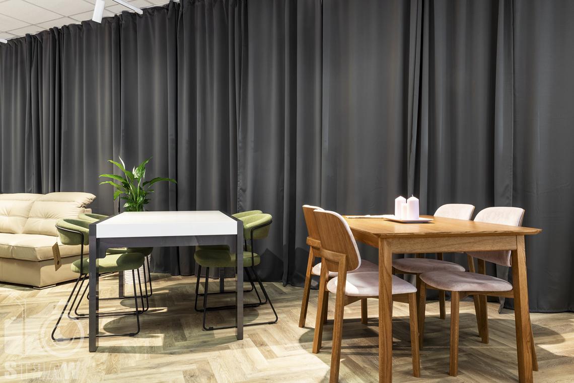 Fotografia wnętrz komercyjnych, zdjęcia sklepu meblowego, drewniany stół w komplecie z drewnianymi krzesłami i jasnymi obiciami.