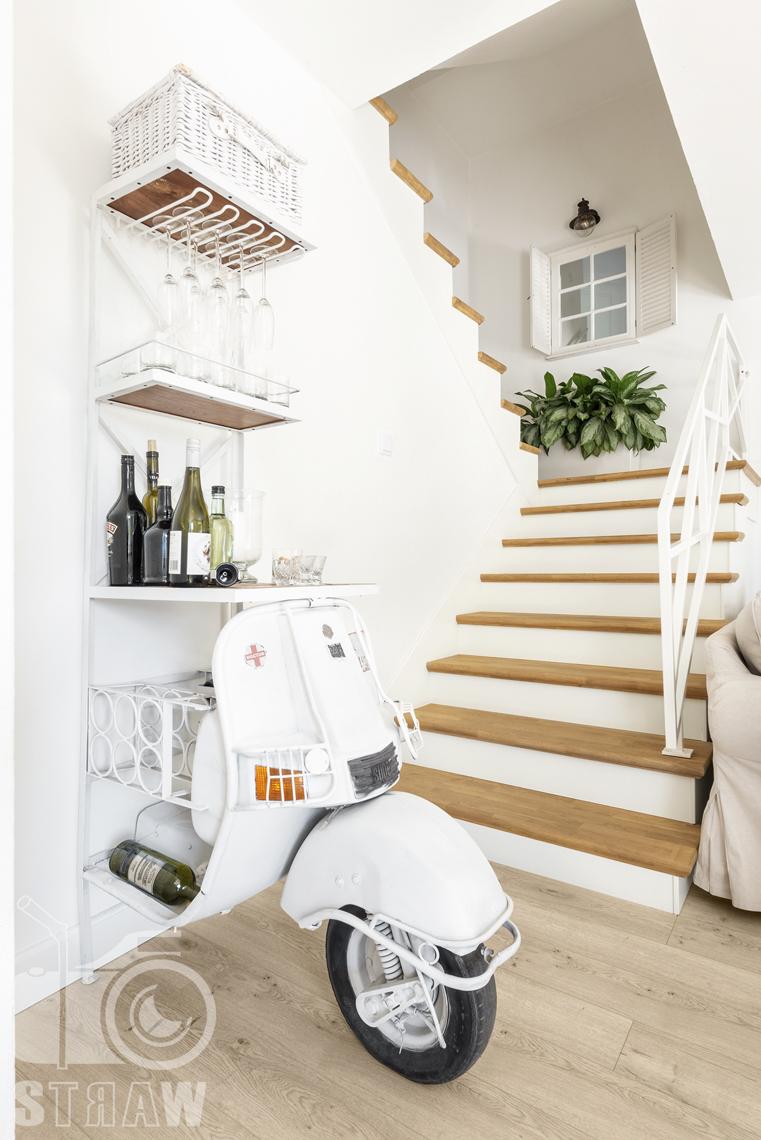 Fotografia wnętrz nieruchomości na sprzedaż Warszawa, barek na alkohol i kieliszki zrobiony ze skutera, schody na piętro.