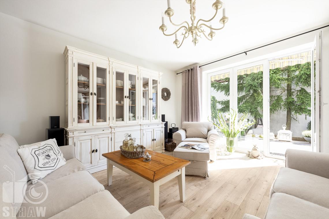 Fotografia wnętrz nieruchomości na sprzedaż Warszawa, salon z sofami, fotelem i stołem, przeszklona komoda, okna.