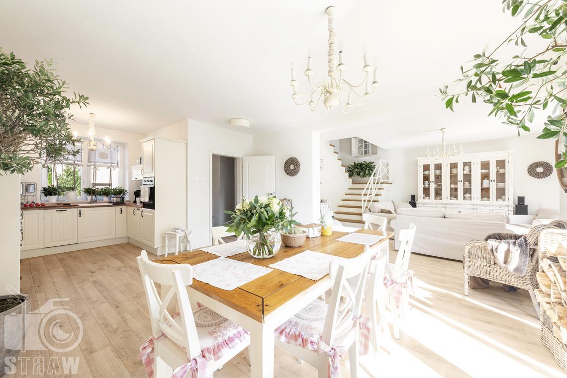 Fotografia wnętrz nieruchomości na sprzedaż Warszawa, jadalnia i stół drewniany, wazon z kwiatami na stole, krzesła z poduchami, kuchnia i salon.