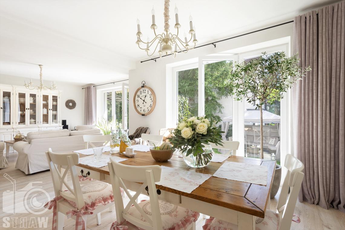Fotografia wnętrz nieruchomości na sprzedaż Warszawa, salon z jadalnią, drewnianym stołem i bukietem róż z kwiaciarni bukieciarnia.