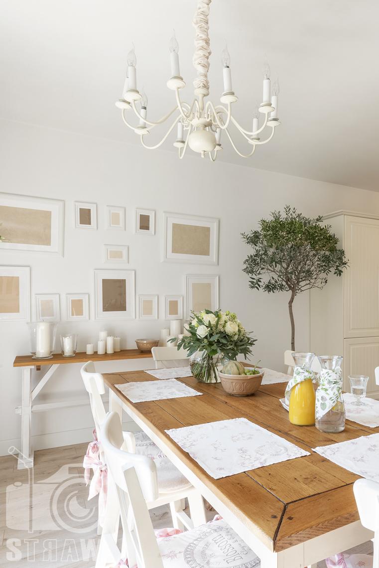 Fotografia wnętrz nieruchomości na sprzedaż Warszawa, drewniany stół w jadalni z bukietem róż na stole.
