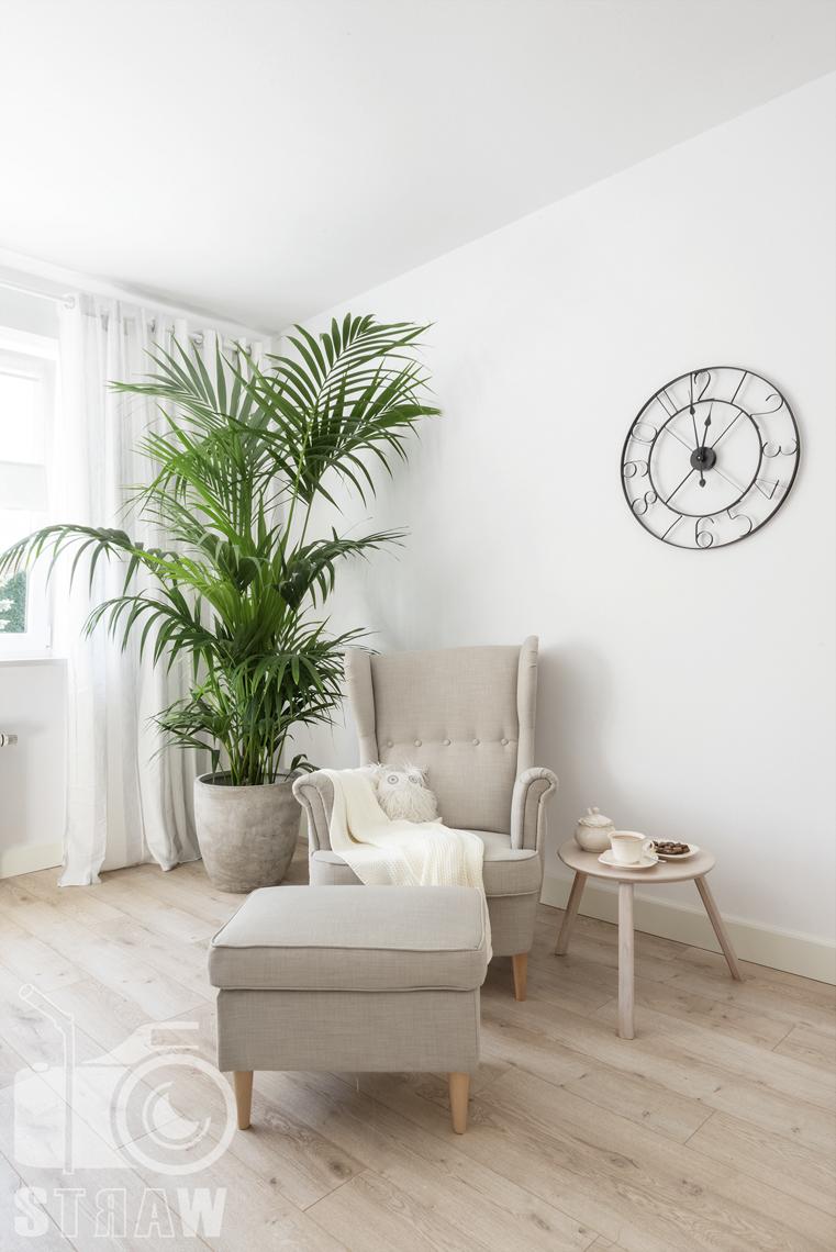 Fotografia wnętrz nieruchomości na sprzedaż Warszawa, zdjęcie fotela w sypialni i zegara na ścianie.