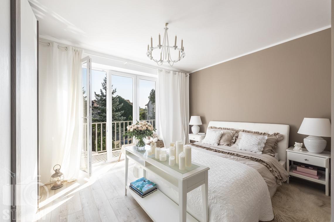 Fotografia wnętrz nieruchomości na sprzedaż Warszawa, sypialnia z żyrandolem w kształcie świecznika, szafka z kwiatami i świecami.