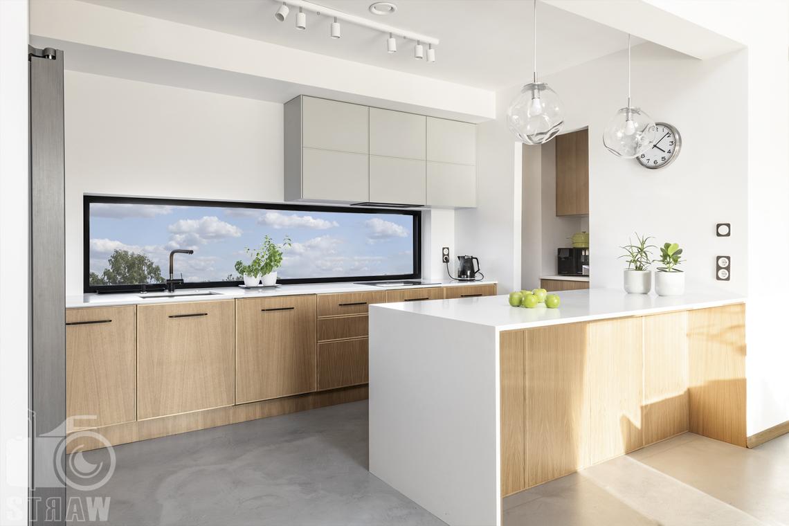 Fotografia wnętrz dla producenta mebli kuchennych, białe wykończenia blatów i fornirowane fronty szafek.