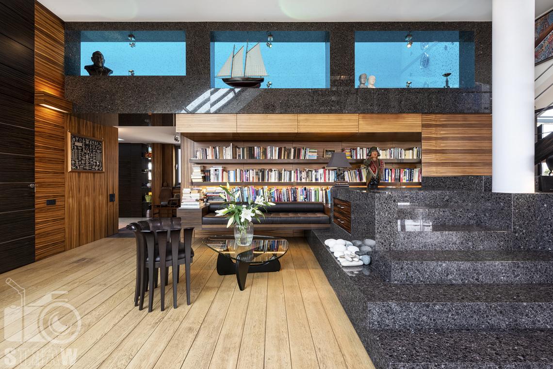 Fotografia wnętrz nieruchomości na sprzedaż, zdjęcia dla biura nieruchomości, biblioteczka z widokiem w stronę przeszklonego wnętrza basenu.