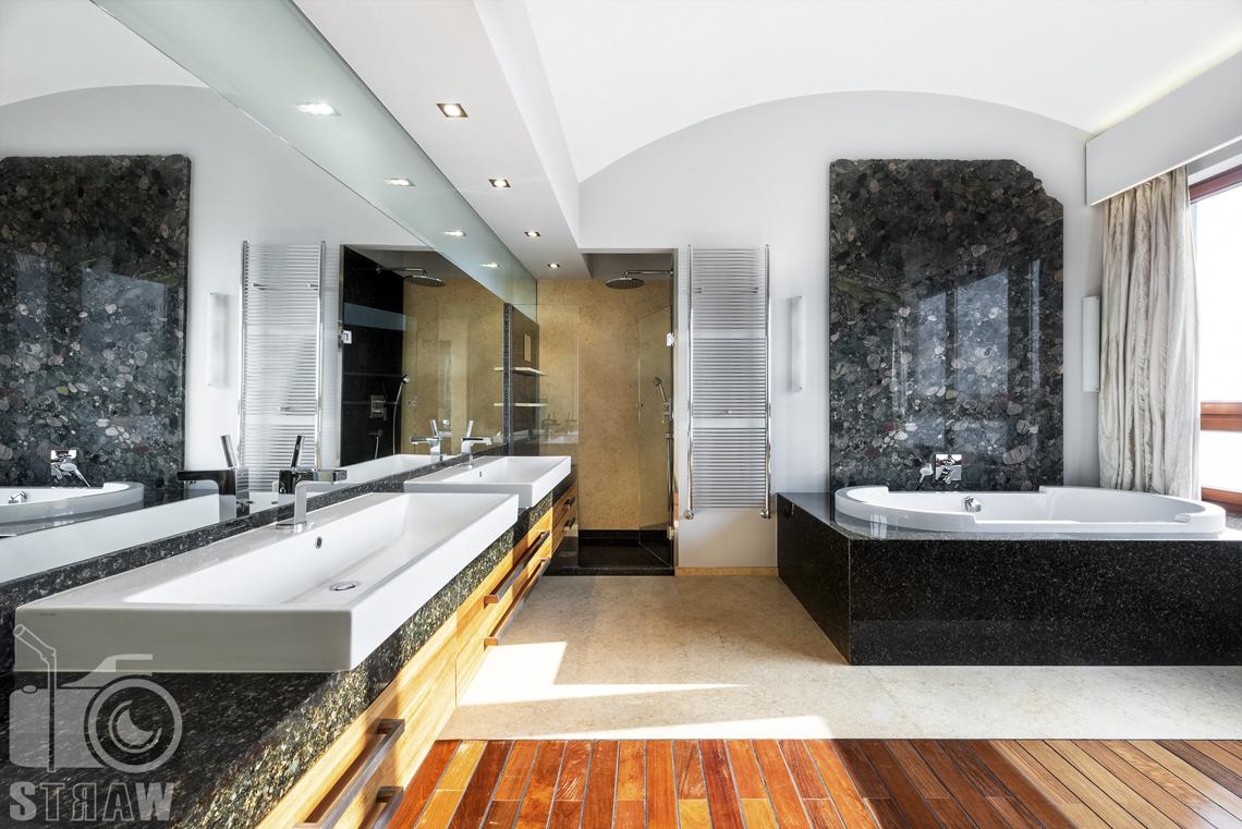 Fotografia wnętrz nieruchomości na sprzedaż, zdjęcia dla biura nieruchomości, łazienka przyległa do dużej sypialni z wanną i dwoma umywalkami.