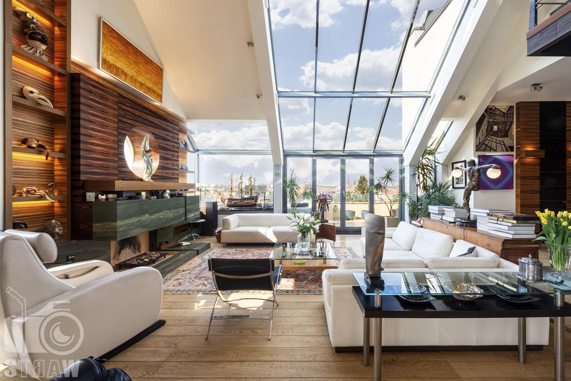 Fotografia wnętrz nieruchomości na sprzedaż, zdjęcia dla biura nieruchomości, salon z ukośnymi oknami do wysokiego sufitu, kominek i małe okrągłe okienko.
