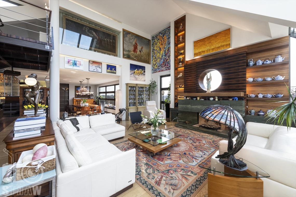 Fotografia wnętrz nieruchomości na sprzedaż, zdjęcia dla biura nieruchomości, salon, dzieła sztuki, kominek i widok na stół w jadalni.